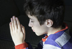Jeune garçon priant avec la foi innocente à son Dieu, concentré religieux images libres de droits