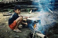 jeune garçon réchauffant une certaine eau pour ses parents photos libres de droits