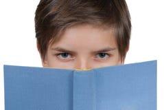 Jeune garçon regardant derrière un livre bleu Photographie stock libre de droits