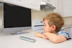 Jeune garçon regardant la TV dans une cuisine Photos libres de droits