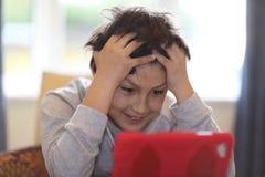 Jeune garçon regardant le comprimé Photo stock