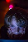 Jeune garçon regardant le comprimé la nuit Images stock