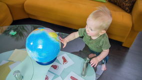 Jeune garçon regardant le globe banque de vidéos