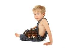 Jeune garçon reposant avec des chiots de briquet sur le sien les genoux Image stock