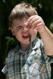 Jeune garçon retenant un lézard Photo stock