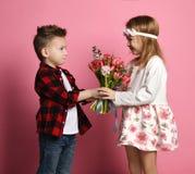 Jeune garçon sérieux dans les blues-jean et des mains rouges de chemise un bouquet de ressort à une petite fille en robe et guirl image stock