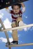Jeune garçon s'élevant sur la gymnastique de jungle Photographie stock libre de droits