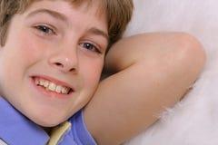 Jeune garçon s'étendant sur la fourrure blanche image stock