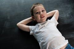 Jeune garçon s'étendant sur le plancher regardant l'appareil-photo et le sourire Concept de construction créatif pour le calendri Photographie stock libre de droits