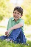 Jeune garçon s'asseyant à l'extérieur Photographie stock libre de droits