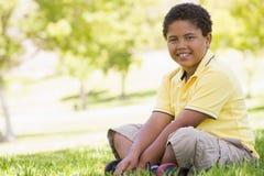 Jeune garçon s'asseyant à l'extérieur Images stock