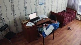 Jeune garçon s'asseyant au carnet dans la chambre de dortoir Vieux lit avec la couverture rouge Téléphone de prise étudiant clips vidéos