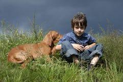 Jeune garçon s'asseyant dans l'herbe Image stock