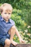 Jeune garçon s'asseyant dans le jardin Photos stock