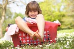 Jeune garçon s'asseyant dans le panier de blanchisserie image libre de droits