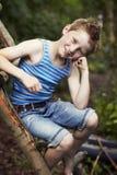 Jeune garçon s'asseyant sur ce dernier en bois, souriant Photo stock