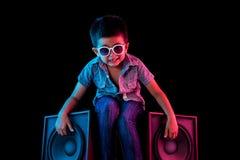 Jeune gar?on s'asseyant sur des haut-parleurs semblant frais avec l'?clairage color? rouge et bleu vif images libres de droits
