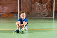 Jeune garçon s'asseyant sur l'attente au sol Photo stock