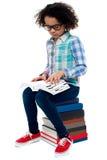 Jeune garçon s'asseyant sur la pile de livres et de lecture Image stock