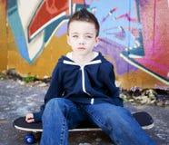 Jeune garçon s'asseyant sur la planche à roulettes Photos libres de droits