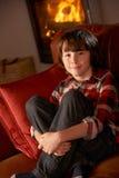 Jeune garçon s'asseyant sur le sofa par le feu de bois confortable Images libres de droits