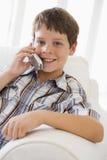 Jeune garçon s'asseyant sur parler de sofa Image stock