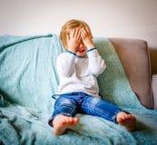 Jeune garçon s'asseyant sur pleurer de divan photo stock