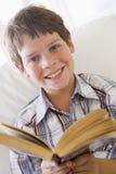 Jeune garçon s'asseyant sur un sofa affichant un livre Photo stock