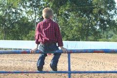 Jeune garçon s'asseyant sur une barrière Photographie stock