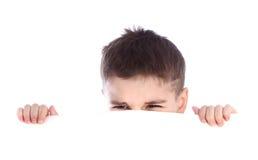 Jeune garçon se cachant derrière un panneau d'affichage et faisant un visage sur l'appareil-photo Images libres de droits