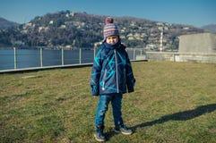 Jeune garçon se tenant sur l'herbe près du lac Como Photographie stock