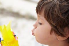 Jeune garçon soufflant sur le moulin à vent photographie stock