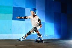Jeune garçon sur des patins de rouleau faisant la glissière contre le mur bleu de graffiti Photos stock
