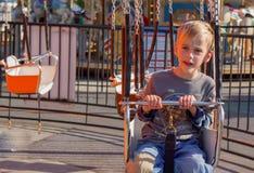 Jeune garçon sur l'oscillation de carnaval photos stock