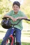 Jeune garçon sur la bicyclette souriant à l'extérieur image libre de droits