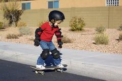 Jeune garçon sur la planche à roulettes Photographie stock libre de droits