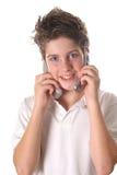 Jeune garçon sur la verticale de deux téléphones portables photo stock