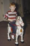 Jeune garçon sur le cheval d'oscillation Photo libre de droits