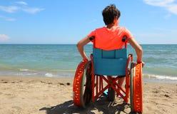 Jeune garçon sur le fauteuil roulant sur la plage photo libre de droits