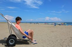 Jeune garçon sur le fauteuil roulant spécial dans l'été sur la plage images libres de droits