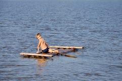 Jeune garçon sur le radeau dans l'eau photographie stock libre de droits