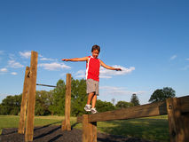 Jeune garçon sur un faisceau d'équilibre Images stock