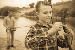 Jeune garçon tenant dessus des poissons de crochet sur la forêt Photos libres de droits