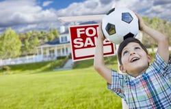 Jeune garçon tenant la boule devant la Chambre et le signe de vente Photographie stock libre de droits