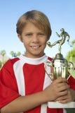 Jeune garçon tenant le trophée du football photos stock