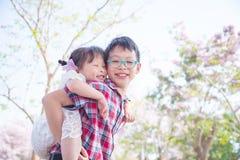 Jeune garçon tenant son dos de soeur dessus Photos libres de droits