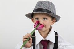 Jeune garçon tenant une fleur et une odeur roses dans l'amour Images libres de droits