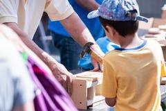 Jeune garçon tenant une maison d'oiseau de bâtiment de marteau photographie stock