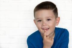 Jeune garçon utilisant la veste bleue indiquant pour être tout à fait dans l'international Photographie stock libre de droits