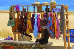 Jeune garçon vendant des marchandises sur la plage Photo libre de droits